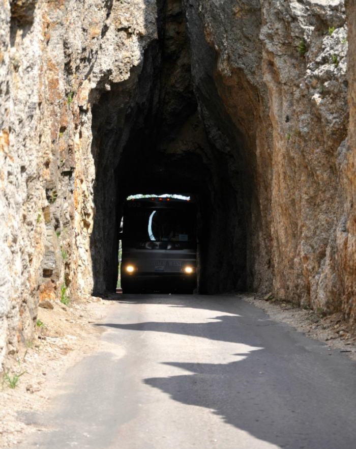 A charter bus squeezing through the tunnel. It just barely fits in...talk about crazy!