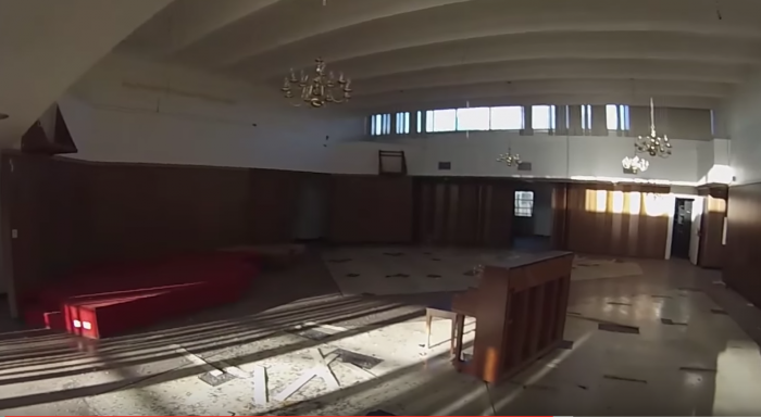 A lone piano stands in a massive hall that must have once served as a recreation area.