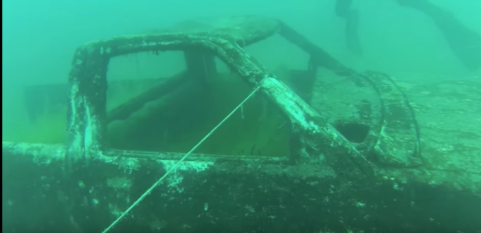 The divers find multiple submerged vehicles, including a firetruck, slowly decaying in the eerie stillness of the quarry.