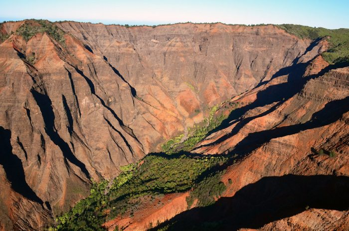 """Over time, the basalt has weathered from its original black hue to Waimea Canyon's signature red. After all, waimea translates to """"reddish water"""" in Hawaiian, surely referring to the canyon's striking color."""