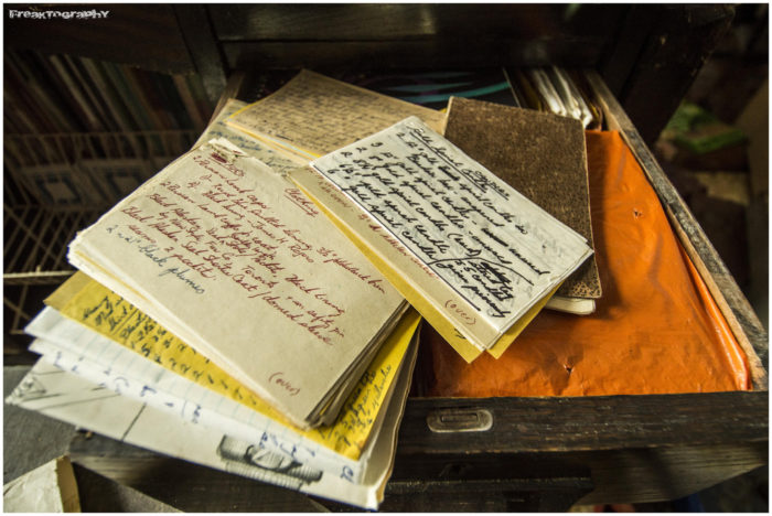 Old, handwritten letters and notes are stacked in piles.
