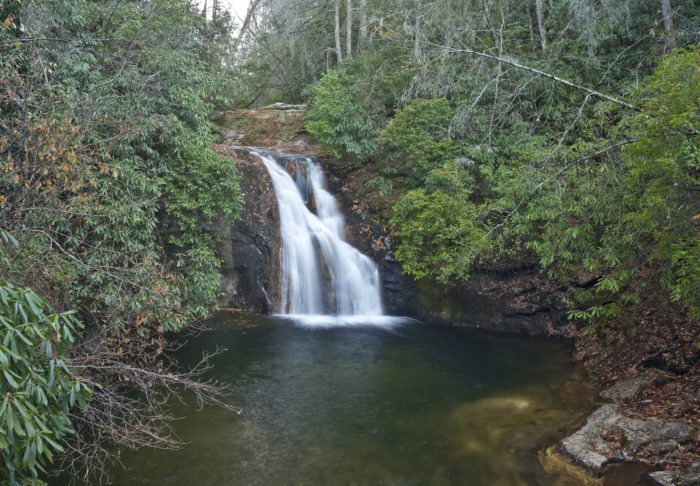 The water from High Shoals Creek cascades down the 20-foot rock cliff, into the deep, blue pool of water below.