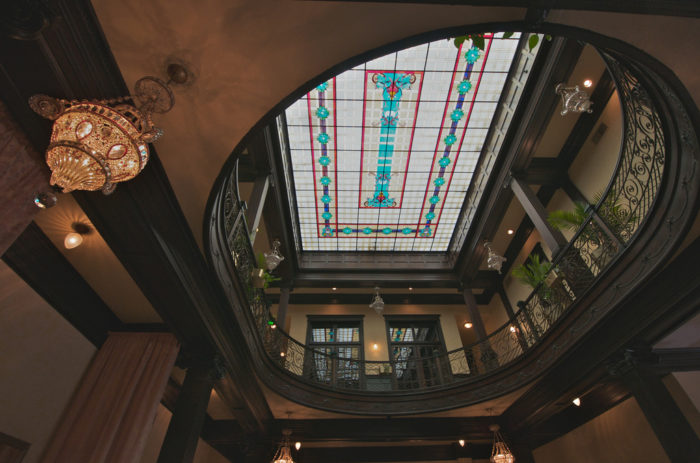 Now, stepping into the Geiser Grand, you are greeted by the hotel as it appeared in its heyday: mahogany woodwork, crystal chandeliers, and an exquisite stained-glass ceiling.