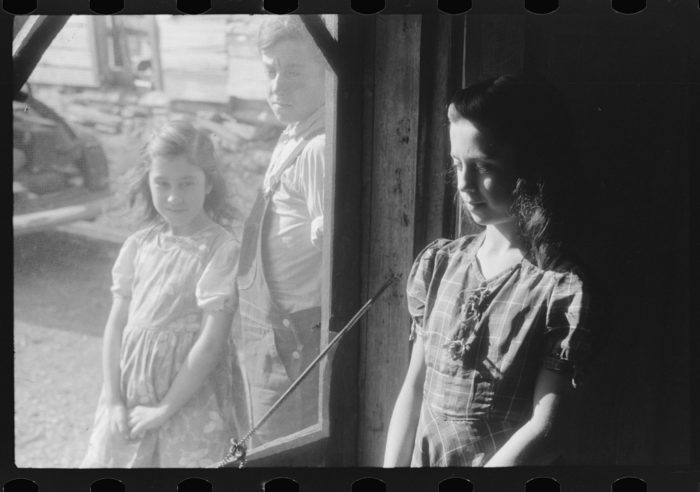 5. These children of French-Canadian potato farmers stand at the back door of their home in Lille.