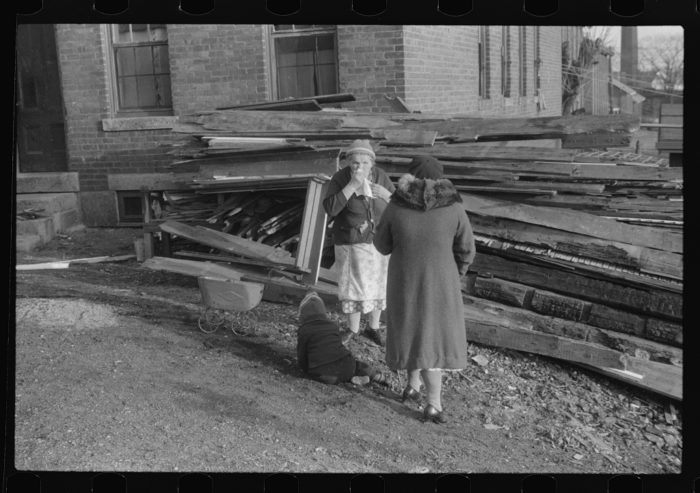 2. Two mill workers stand outside their work in the town of Asheville.