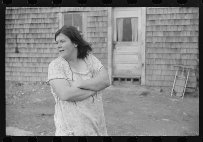 4. A woman stands outside her home in the 1930s.