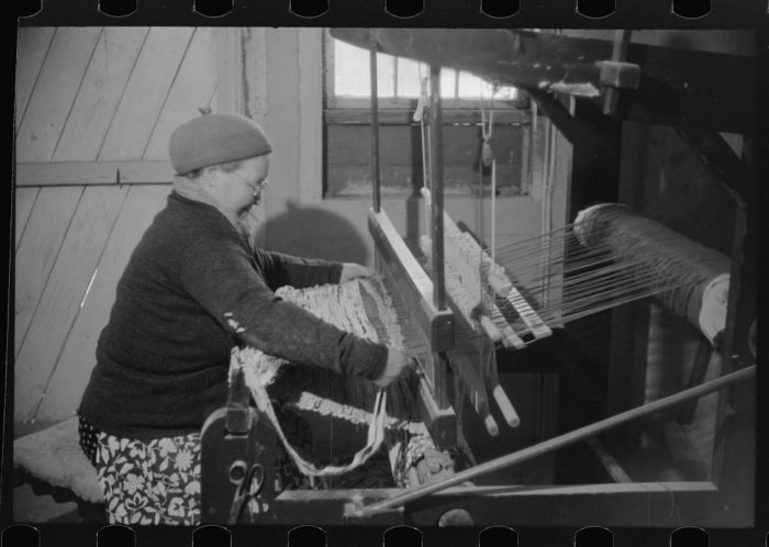 8. The wife of a poultry farmer works at her old fashioned loom in this old photo.