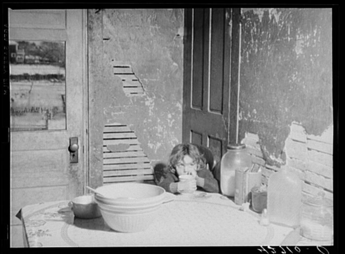1. A child of a farmer sits in a decaying home in the 1930s.