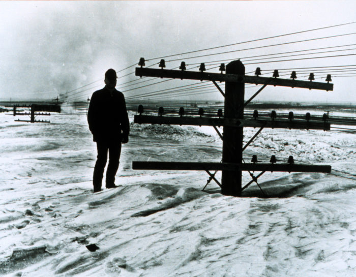 4. Man standing next to a utility pole after a massive blizzard in Jamestown, 1966