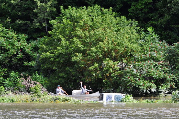 Some people exit their property by canoe as they paddle past a submerged full-size truck.