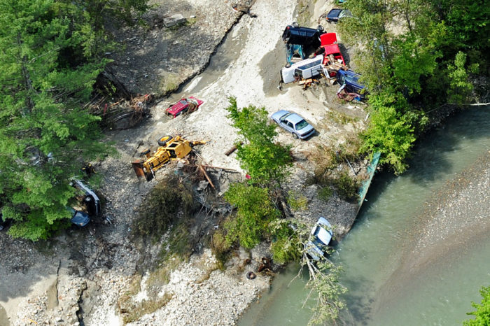 Cars and a tractor look like toys from the air as they are jumbled about and buried in sand and silt.
