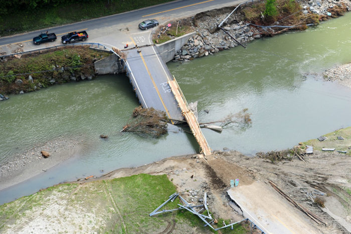 A makeshift walking bridge allows access to Route 100.