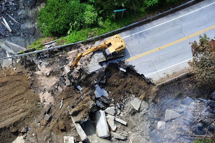 A backhoe works to repair a huge washout just outside Pittsfield.