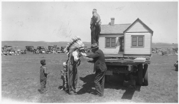 6. Salesman showing his scale model house to a Native American resident, 1940