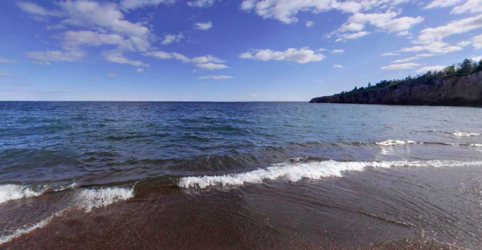 With gorgeous blue water and stunning red pebbles - it's easy to be mesmerized by the views from this beach.
