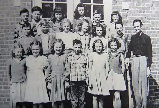The brick school in town, built in 1916, replaced the wooden building built in 1906. These children are standing in front of their new school building.
