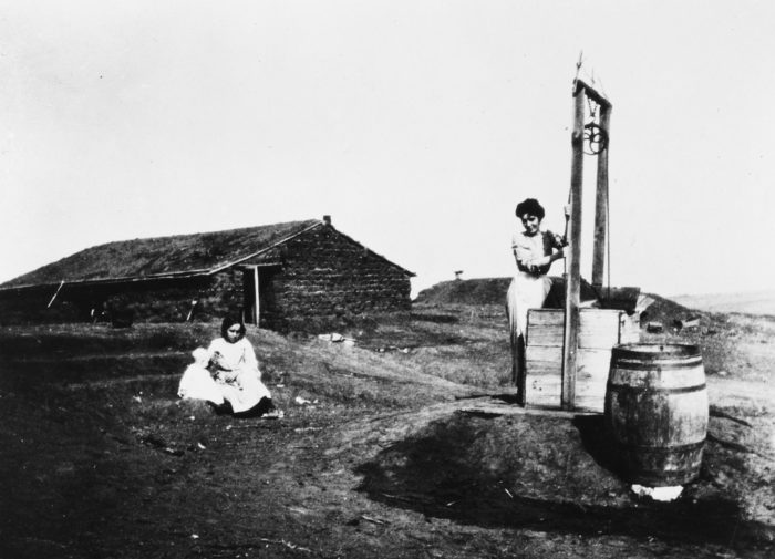 12. Woman drawing water at a well, 1900.