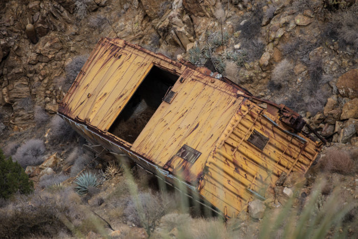 The drama of this spot isn't limited to the bridge itself. Abandoned rail cars lie scattered across the canyon below.