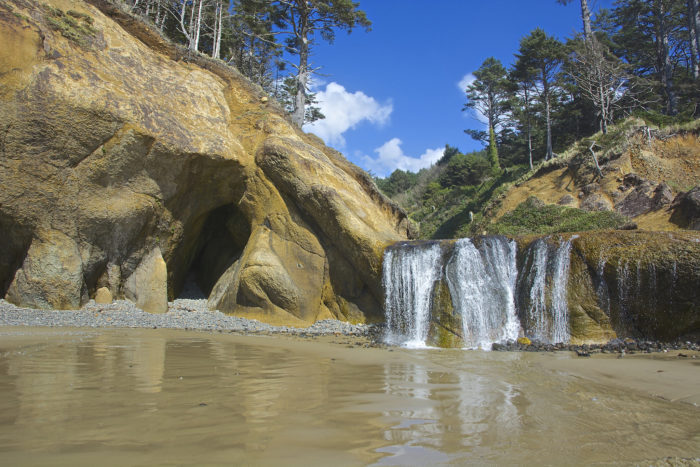 A leisurely half-mile walk from the parking lot will lead you to the enchanting Hug Point Waterfall.