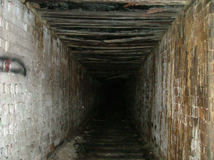 ...and deep within the tunnel, it becomes rectangular and the arched brick ceiling transitions into a flat wooden ceiling. Eventually, the tunnel dead-ends.