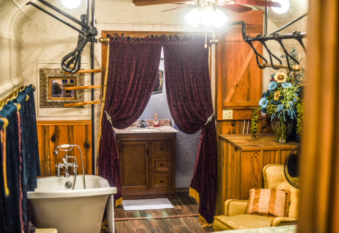 Even the 2 bathrooms are uniquely decorated with velvet drapes, clawfoot bathtub and a rock shower.