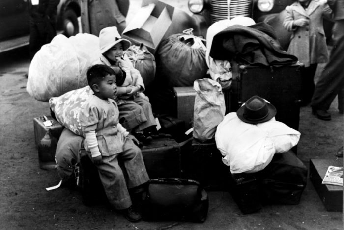 9. Small children in Los Angeles surrounded by piles of luggage as they wait to be evacuated to relocation camps during the war.