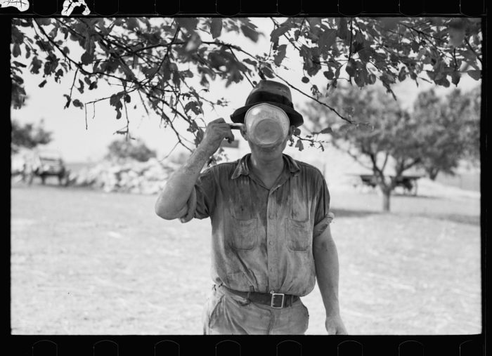 10. A farmer takes a water break during a hot day in 1937.