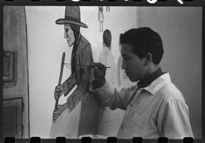 6. A native to the area painting a mural in a school in Pine Ridge, South Dakota, 1940