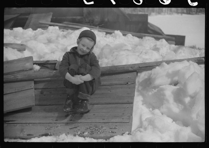 18.  Young daughter of Frank H. Shurtleff sitting outside sugar house where sap from maple trees is boiled down into maple syrup.
