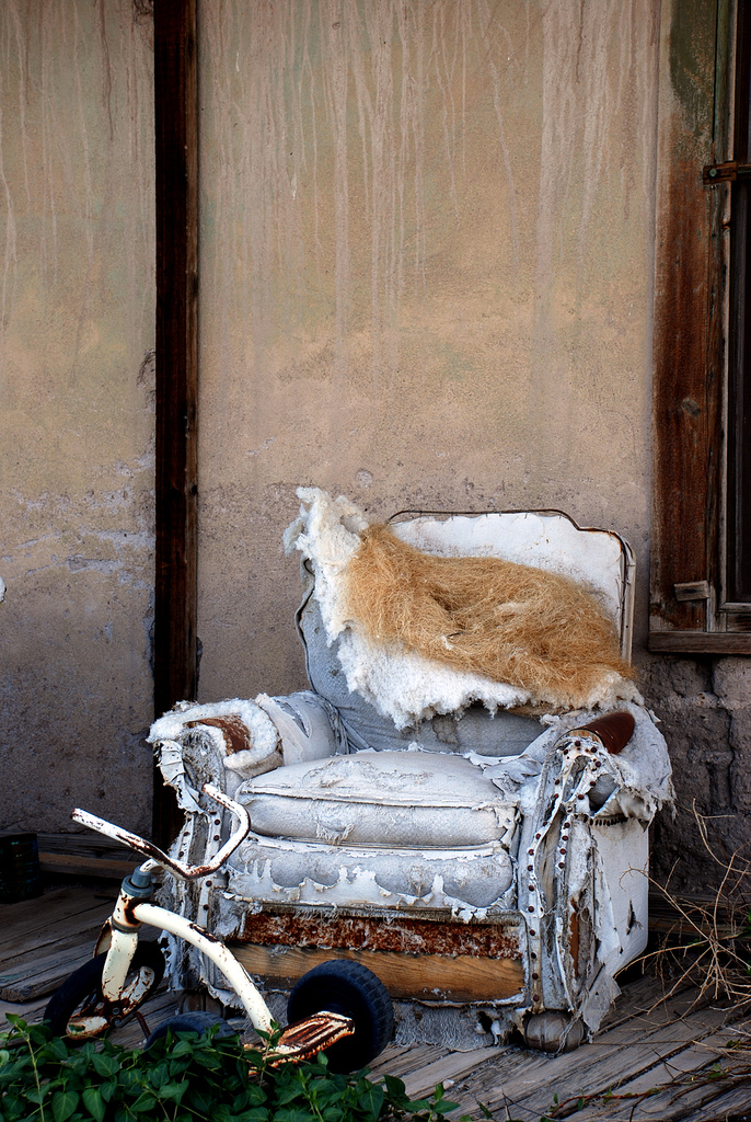 Shells of buildings still stand, windows long gone. An armchair molders on a front porch.