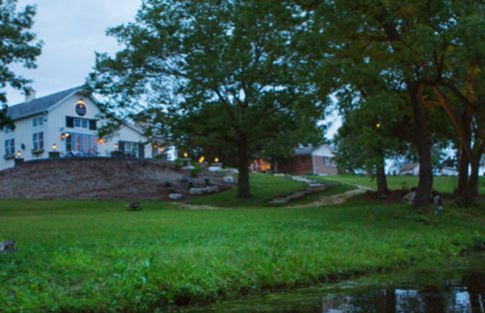 Stone Soup Cottage sits atop a small hill across from a quaint pond.