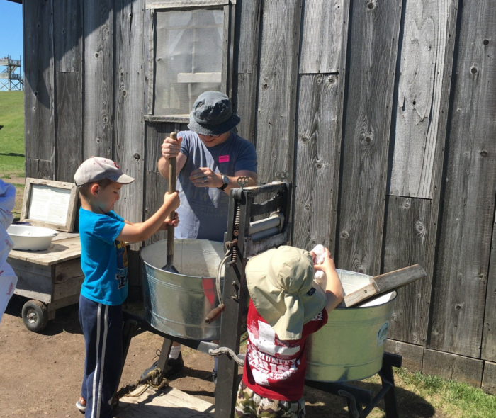 Some of the many hands-on activities including washing laundry the old fashioned way, making a corn husk doll, driving a covered wagon team, and more.