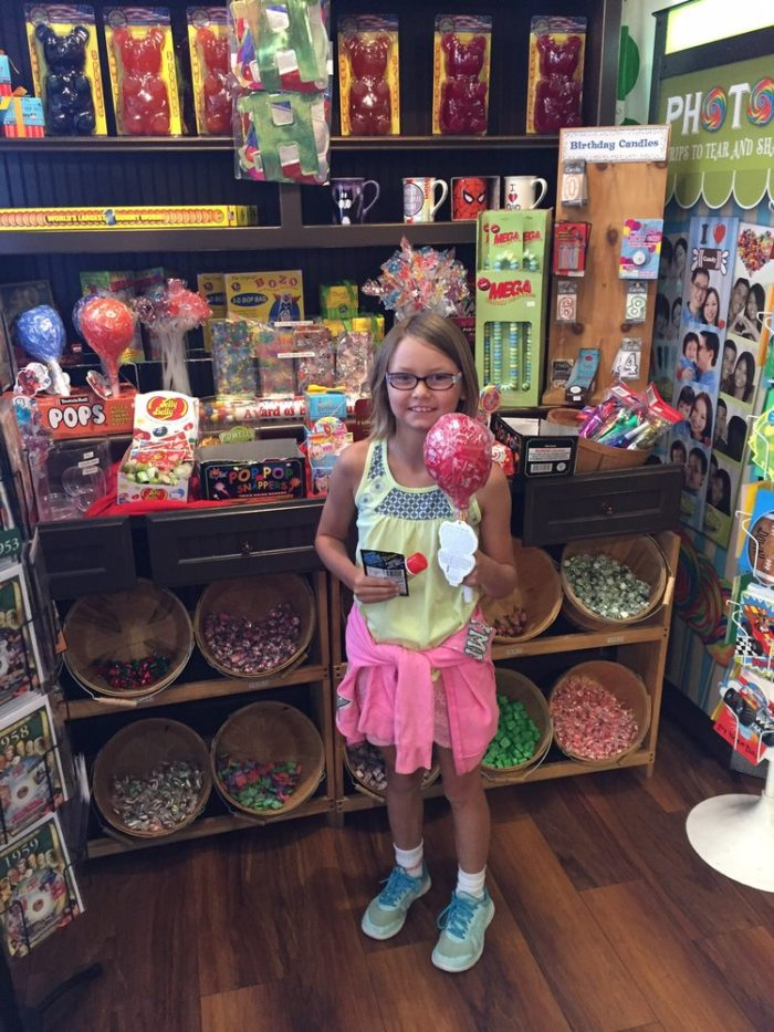 Do you remember what it was like to step inside a candy store? When was the last time you escorted a child into one? This little nugget is over the moon excited over discovering a sucker the size of her head!
