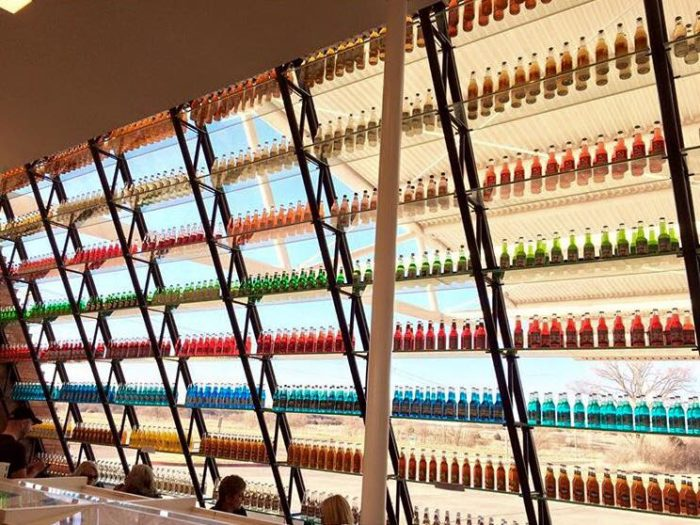 The inside is just as cool as the outside. The massive glass windows are lined with sleek shelves holding hundreds of glass soda bottles - all arranged by color.