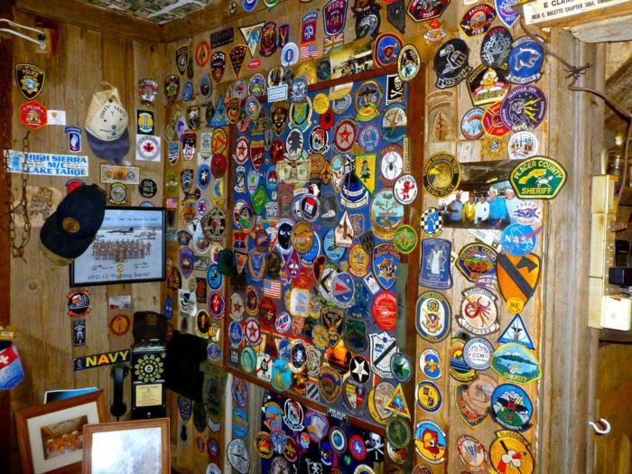 The wall is covered with patches from the police, fire and military personnel who have passed through town.