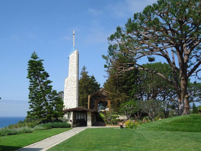 As you first approach this chapel, it looks similar to others you've seen. Its rock spire and cross are standard, familiar features. From far down the path, you can't see the Glass Church very well.