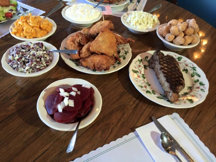 The menu boasts Famous Fried Chicken, Roasted Turkey, Shrimp, Broiled or Fried Fish, T-bone or New York Strip Steaks, Pork Chops, and even Liver, as well as comforting sides like hot corn fritters, mashed potatoes and gravy, and creamy cole slaw.