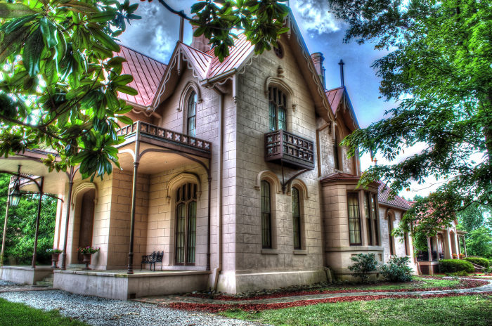 Impressive features of Airliewood include pink-stuccoed walls designed to look like massive blocks of stone, intricate embellishments, such as carved bargeboards and finials, arched windows, and a cast iron fence, which is identical to the one at West Point Military Academy.