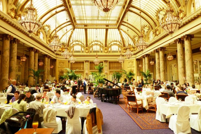 The main dining area is part of a Tiffany-glass-domed garden court that is punctuated by marble-wrapped columns.
