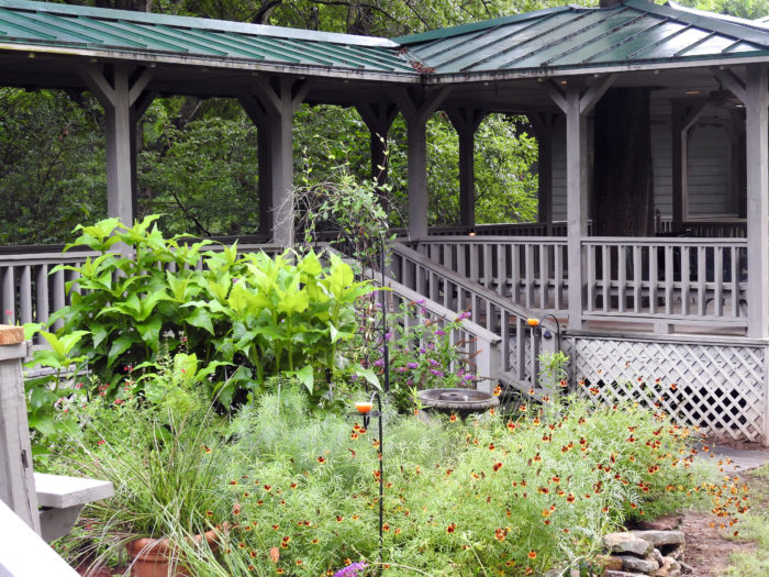 The lodge features a covered walkway and gazebo and is surrounded by a beautiful garden.