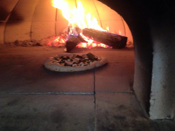 The pizza is baked in a wood fired oven.