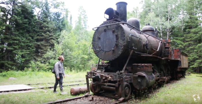 As the explorer approaches the site of the trains, old railroad tracks and train equipment start to appear in the underbrush.