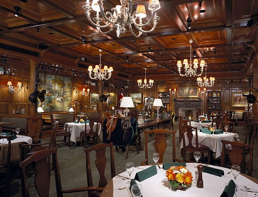 The walls are lined with equestrian scenes, while intricate chandeliers hang overhead.