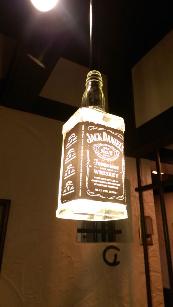 Your cell is lit with an interesting liquor bottle fixture.