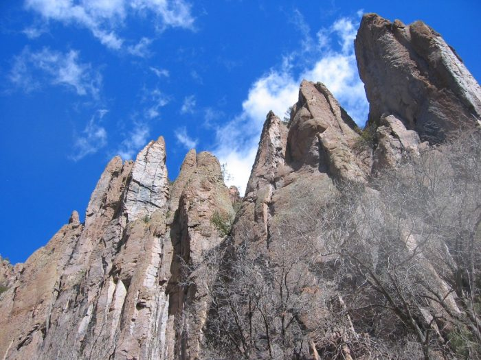 Follow the West Fork Gila River as it passes through a gorge and gaze up at the towering rock face.