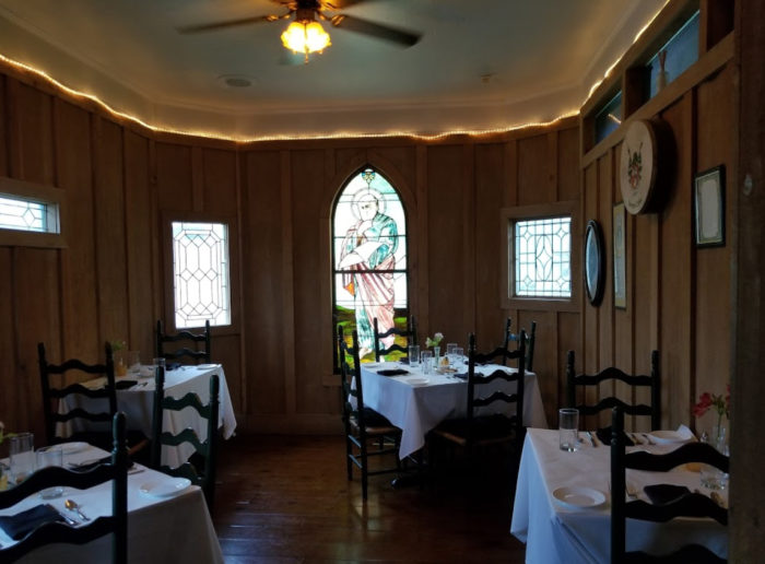 The Understated Tables And Any Other Attempts At Decor Take A Back Row Seat To Windows Shaped In Traditional Gothic Arch Style Filled With